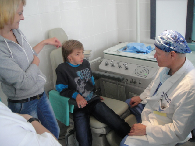 Dr. Peter Adamson with young patient and mother